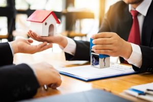 House real estate sell agent reviews the documents that have been approved for the home buyer loan, local movers